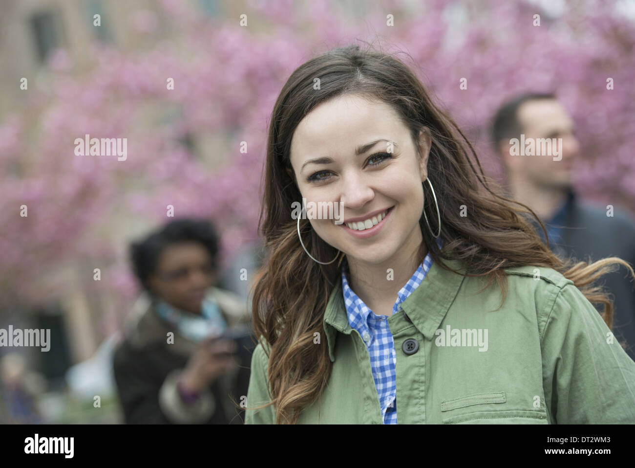Cherry blossom trees in the park A young woman in an open necked shirt smiling and looking at the camera - Stock Image