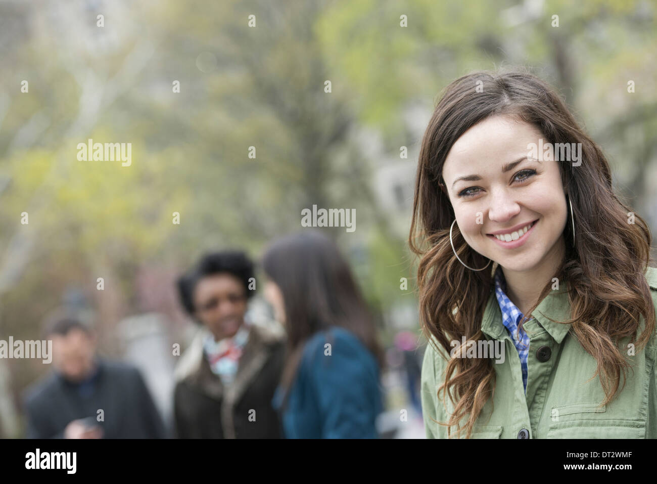 A group of people in the park A young woman in an open necked shirt smiling and looking at the camera - Stock Image