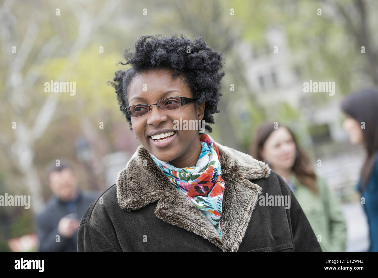 A group of people in a city park A young woman in a coat with a large collar smiling and looking at the camera - Stock Image