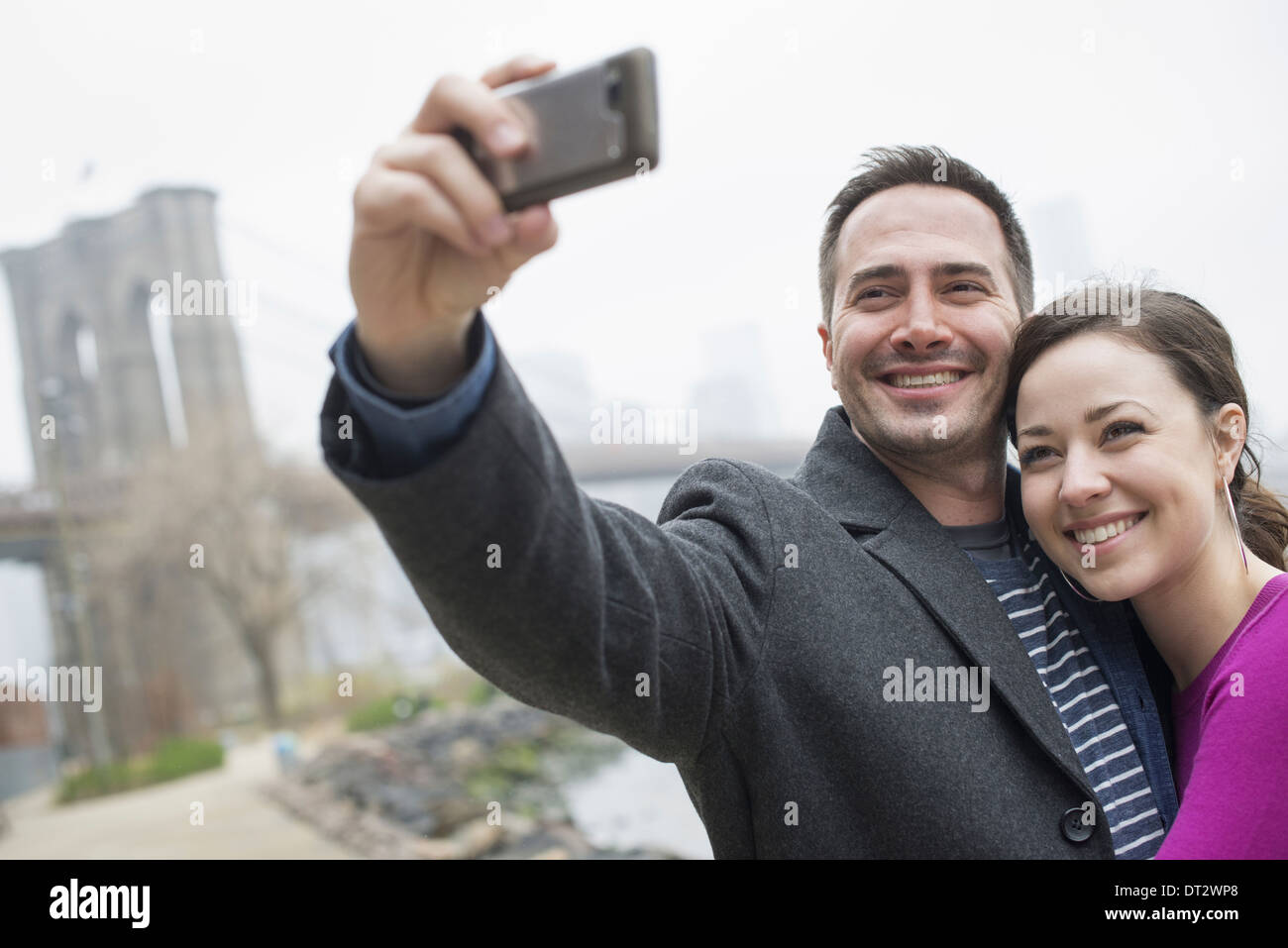New York city The Brooklyn Bridge crossing over the East River A couple taking a picture with a phone a selfy of themselves - Stock Image