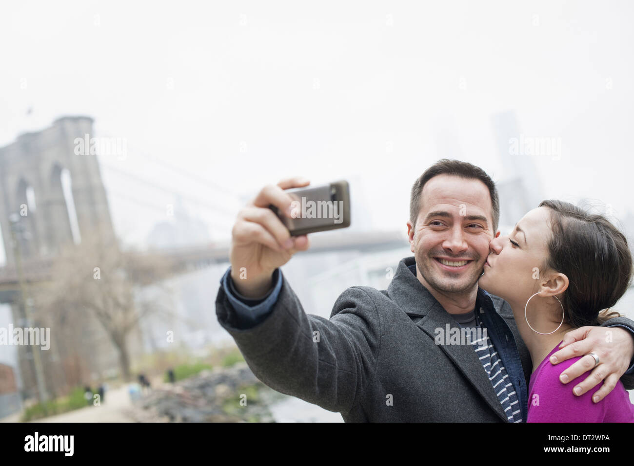 Brooklyn Bridge crossing over the East River A couple taking a picture with a phone a selfy of themselves Stock Photo