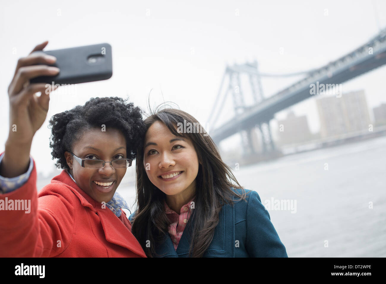 The Brooklyn Bridge crossing over the East River A couple two women taking a picture with a phone a selfy of themselves - Stock Image