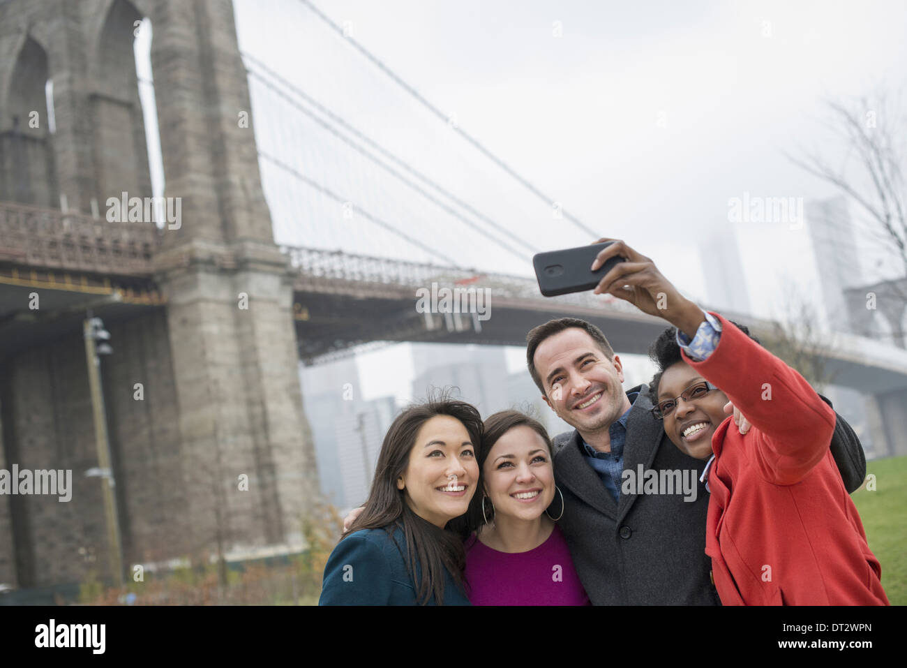 New York city The Brooklyn Bridge crossing over the East River Four friends taking a picture with a phone a selfy of themselves - Stock Image