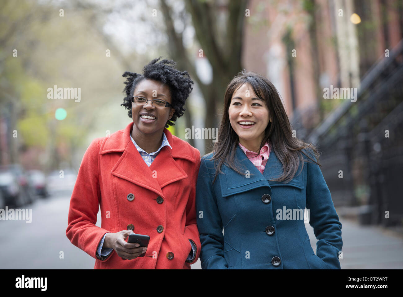 Two women side by side on a city street One holding a cell phone - Stock Image