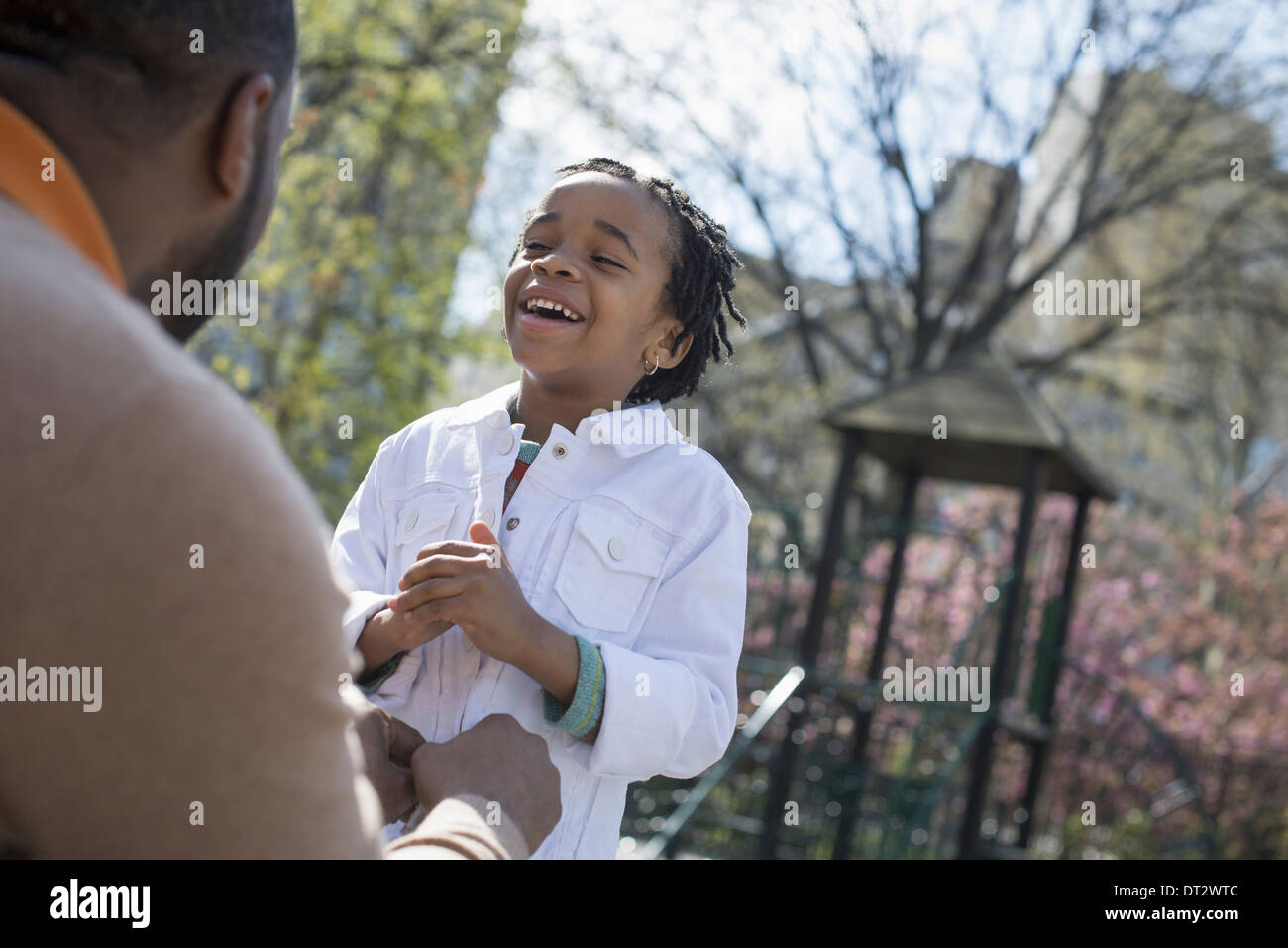 A father kneeling and buttoning his son's jacket - Stock Image