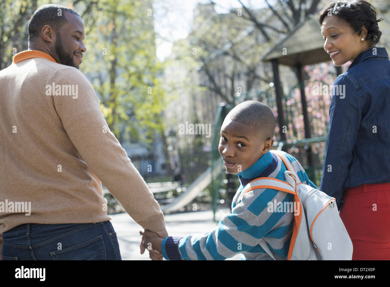 Sunshine and cherry blossom A boy looking over his shoulder between his parents - Stock Image
