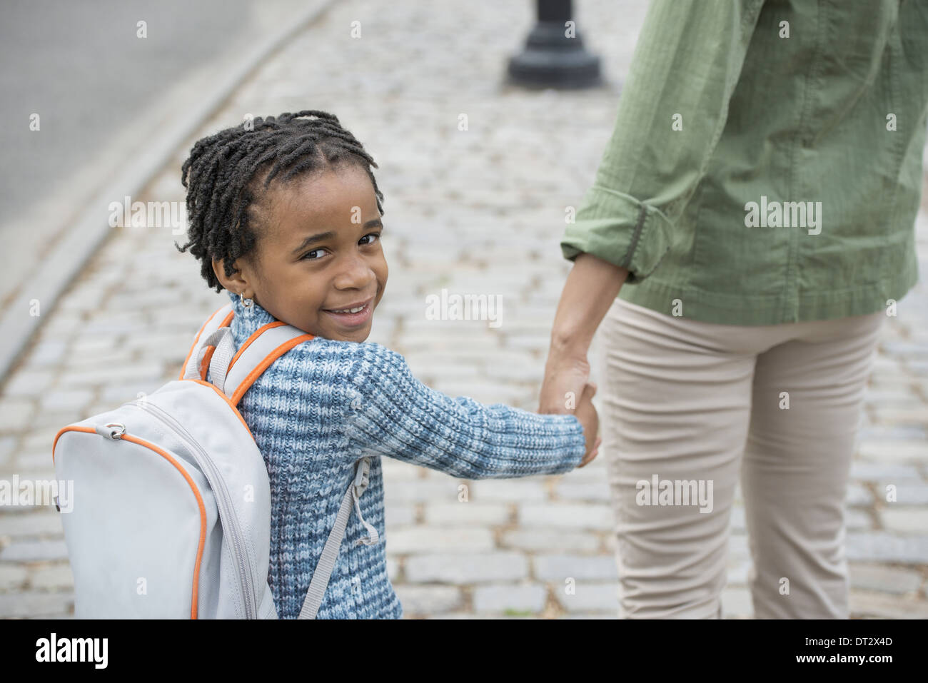 New York City Sunshine and cherry blossom A boy wearing a school bookbag and walking hand in hand with a woman - Stock Image