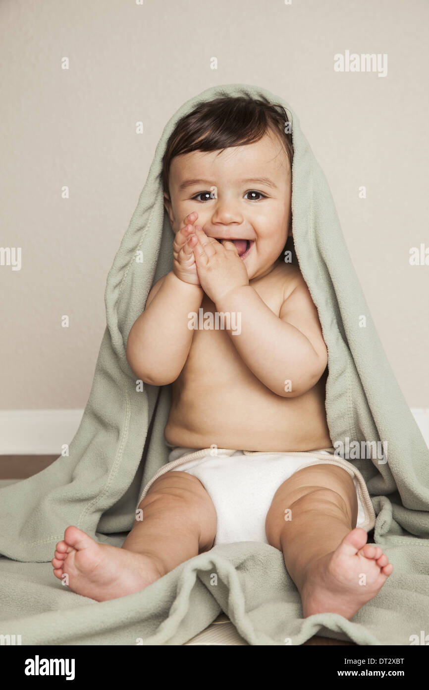 A young 8 month old baby boy wearing cloth diapers sitting on the floor A cot blanket over his head - Stock Image