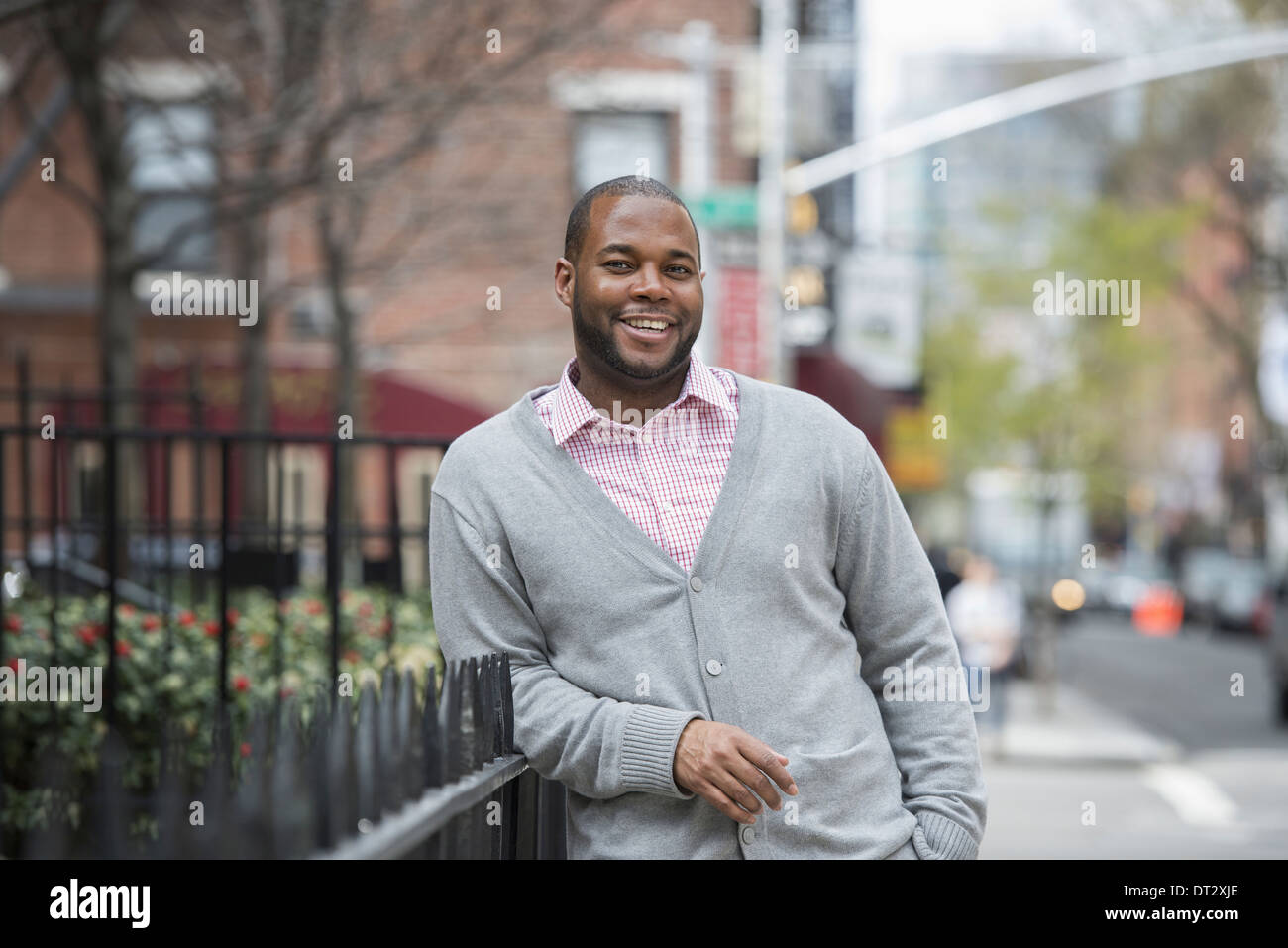 A man leaning against a railing smiling - Stock Image