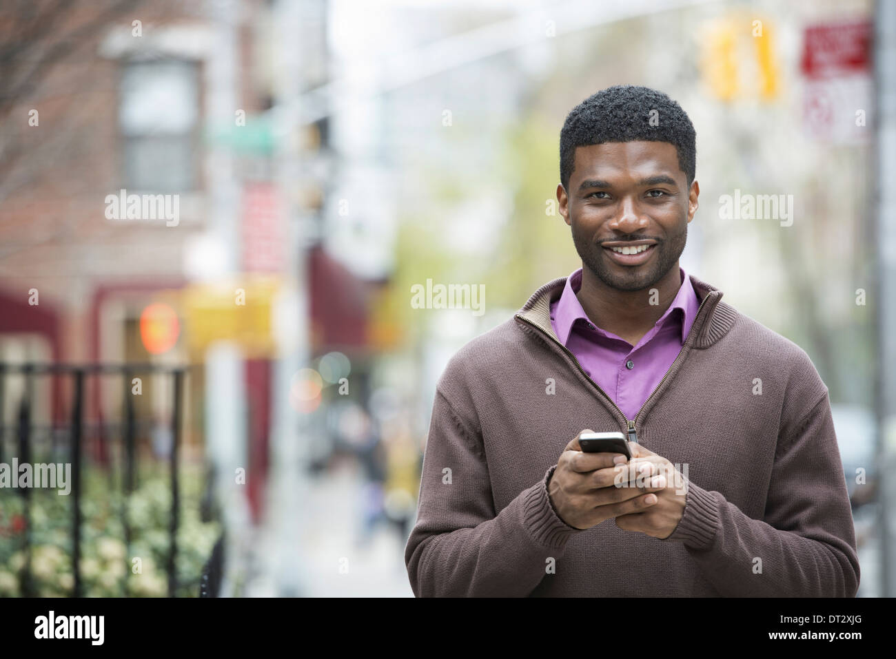 A young man holding his phone and smiling at the camera - Stock Image