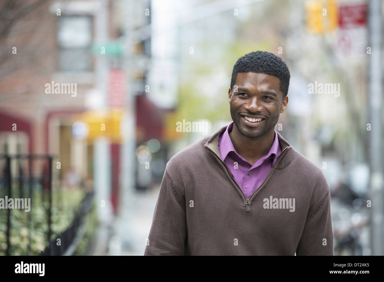 A young man wearing a purple shirt and jersey smiling - Stock Image
