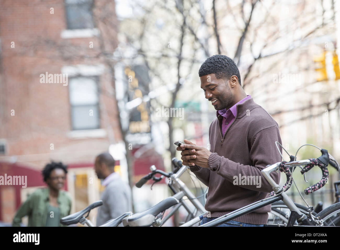 A young man checking his phone and texting Cycle rack and stored bicycles - Stock Image