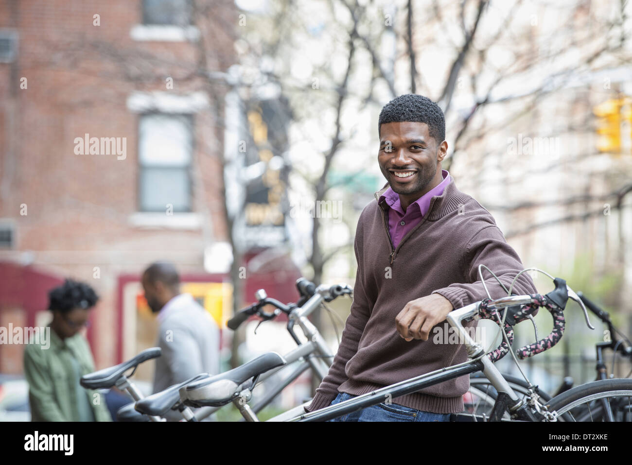 A young man smiling at the camera Bicycle rack - Stock Image