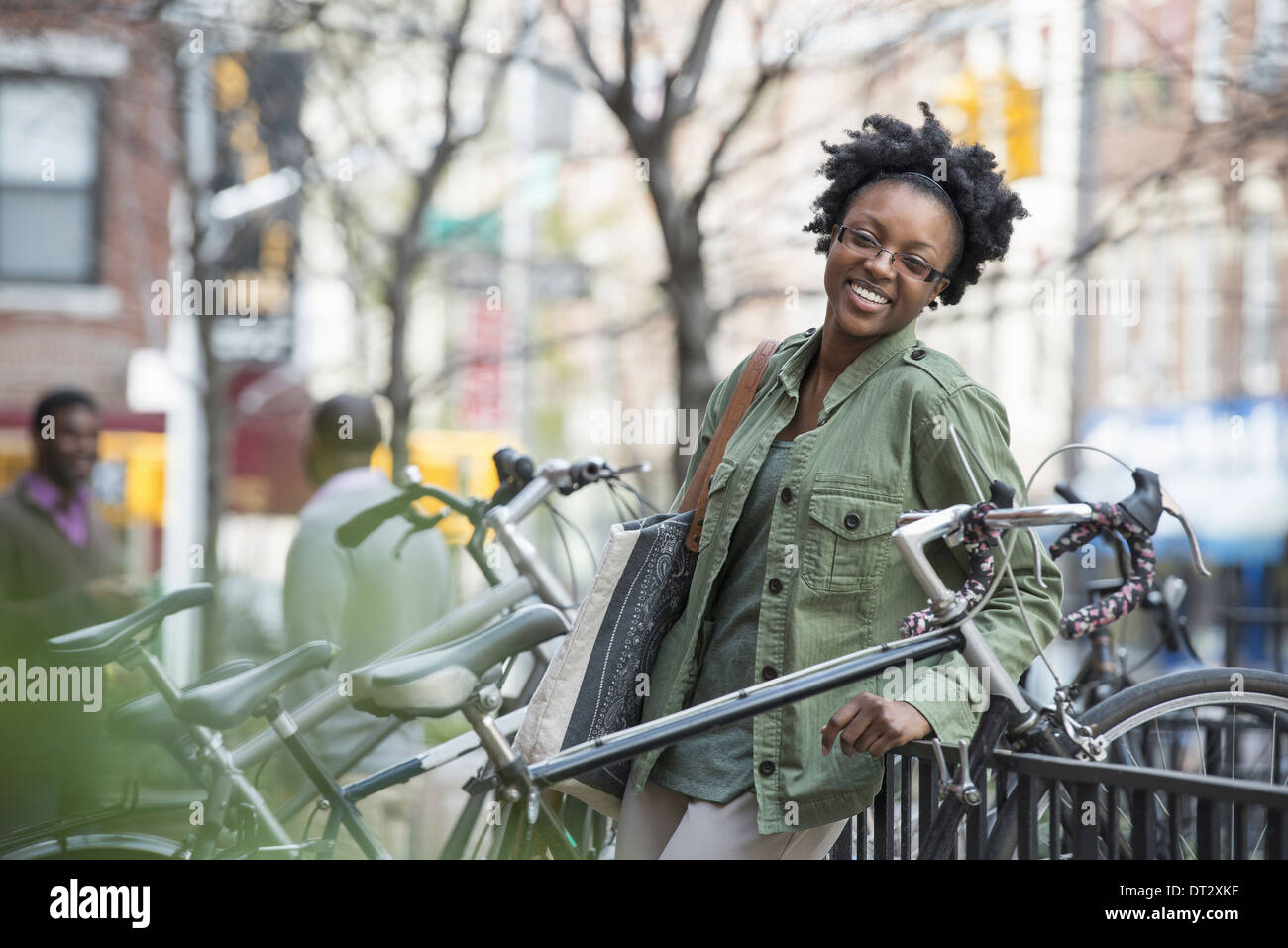 A woman leaning against a railing beside a bicycle rack - Stock Image