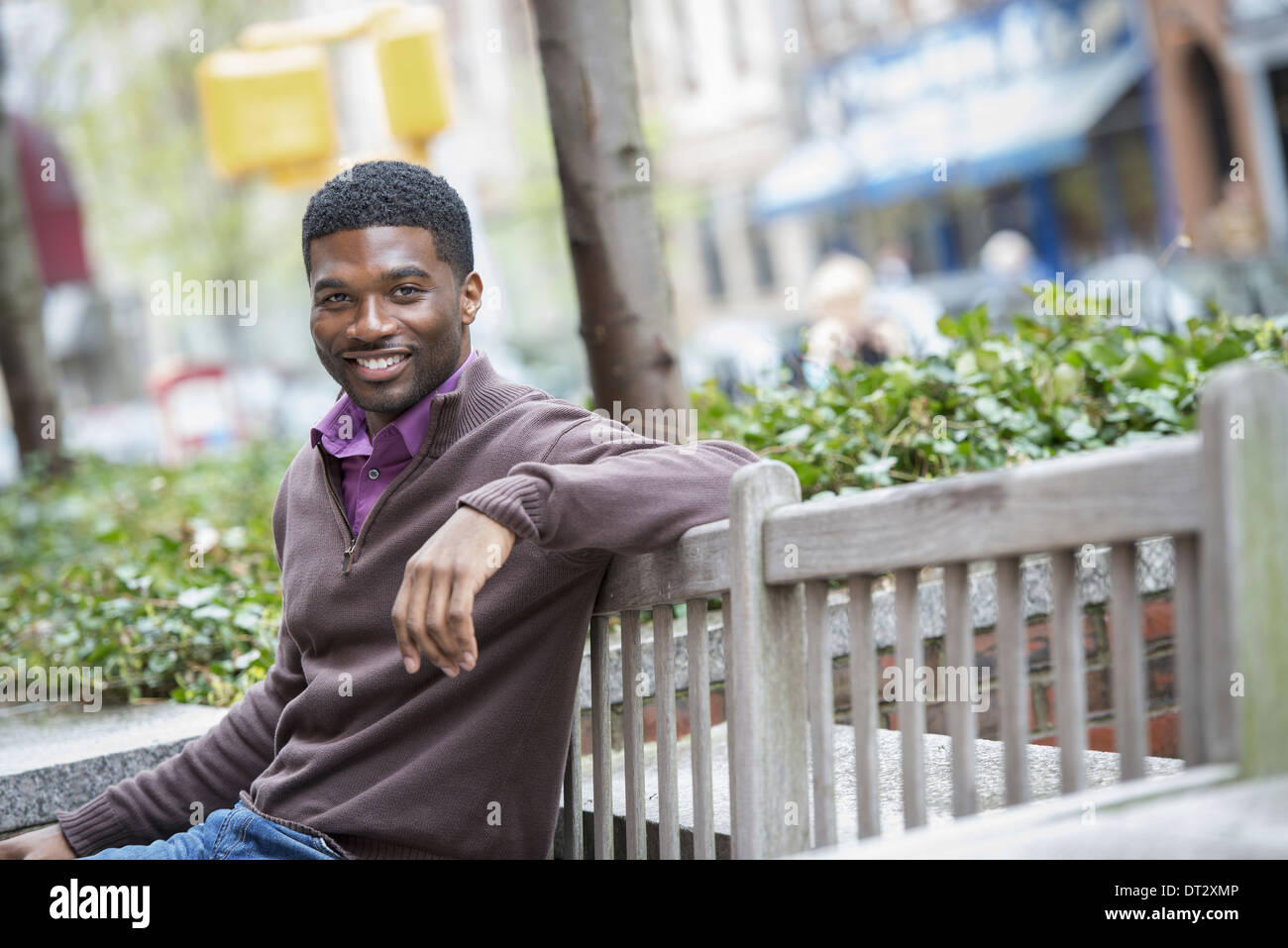 A young man seated on a bench - Stock Image