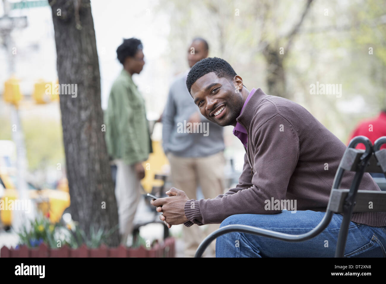 A young man on a bench and a group in the background - Stock Image