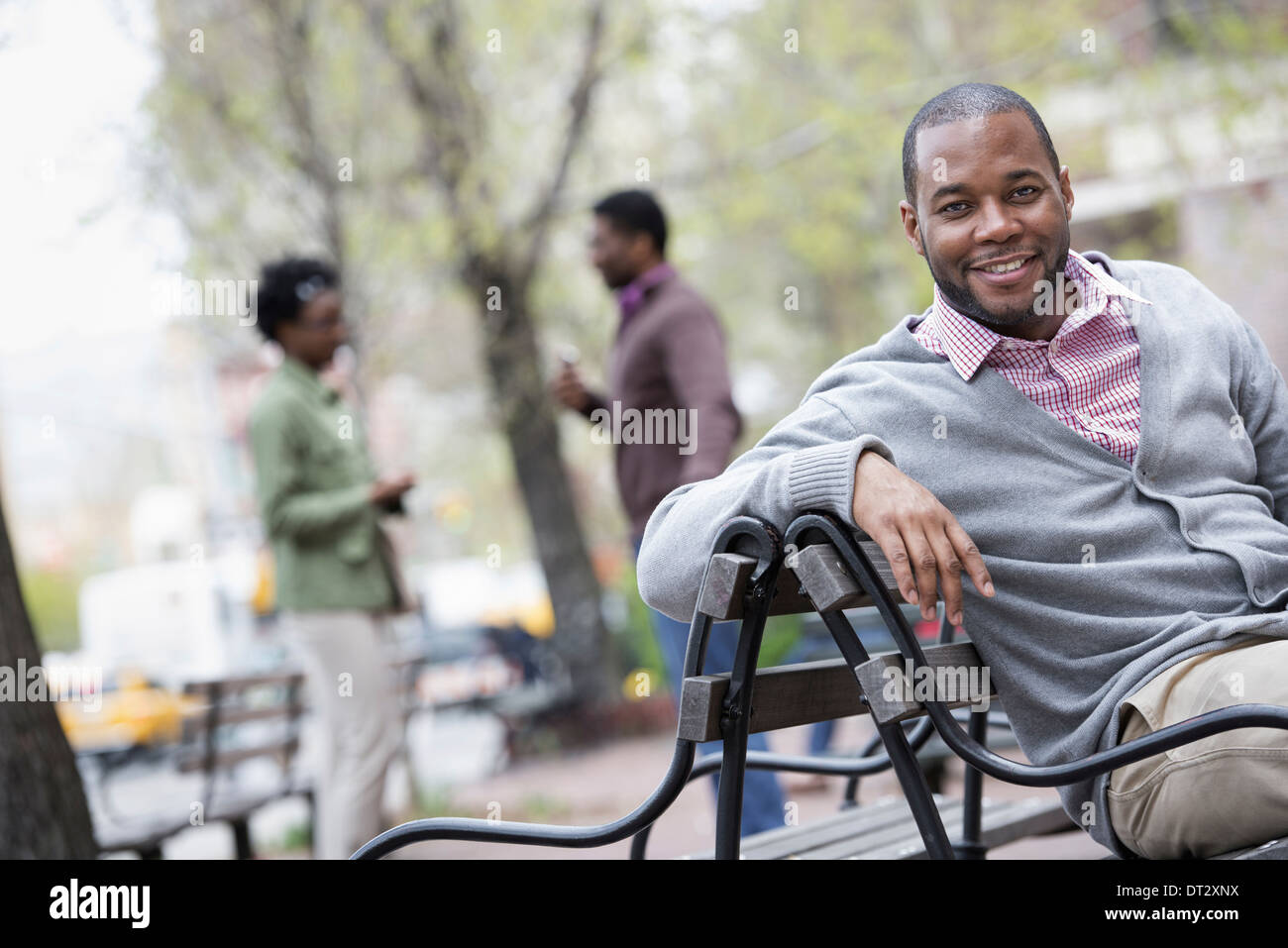 A man seated on a bench with two people in the background - Stock Image