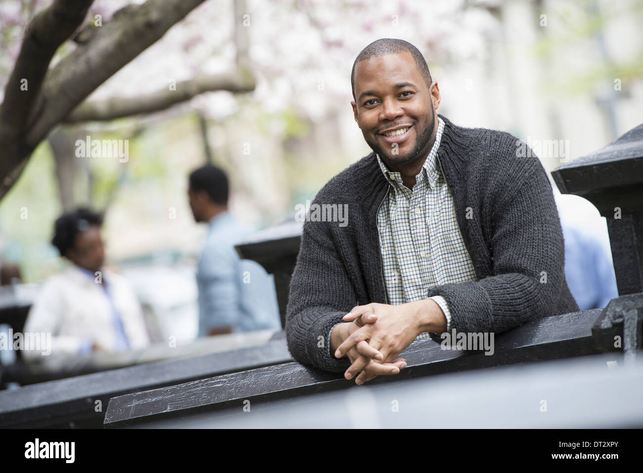 A man seated at a table and two people in the background - Stock Image