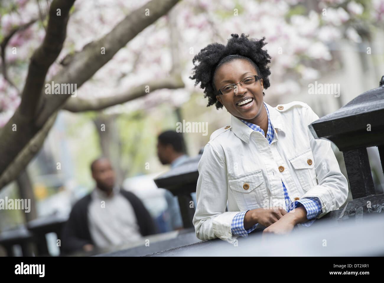 A woman seated at a table with two men in the background - Stock Image