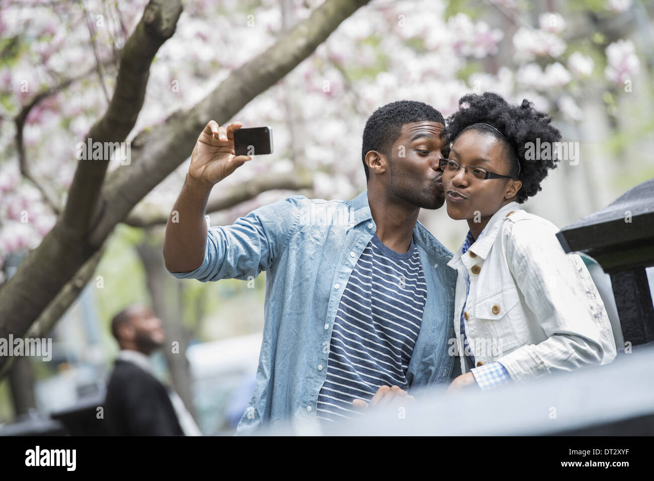 A man kissing a woman and taking a photograph with a handheld mobile phone - Stock Image