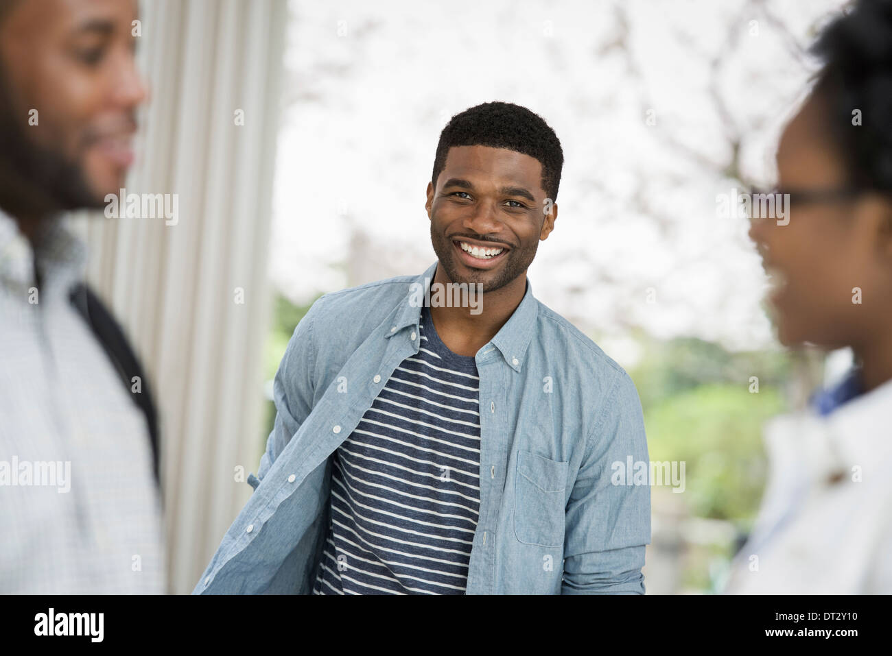 A man looking at the camera with two people in the foreground - Stock Image