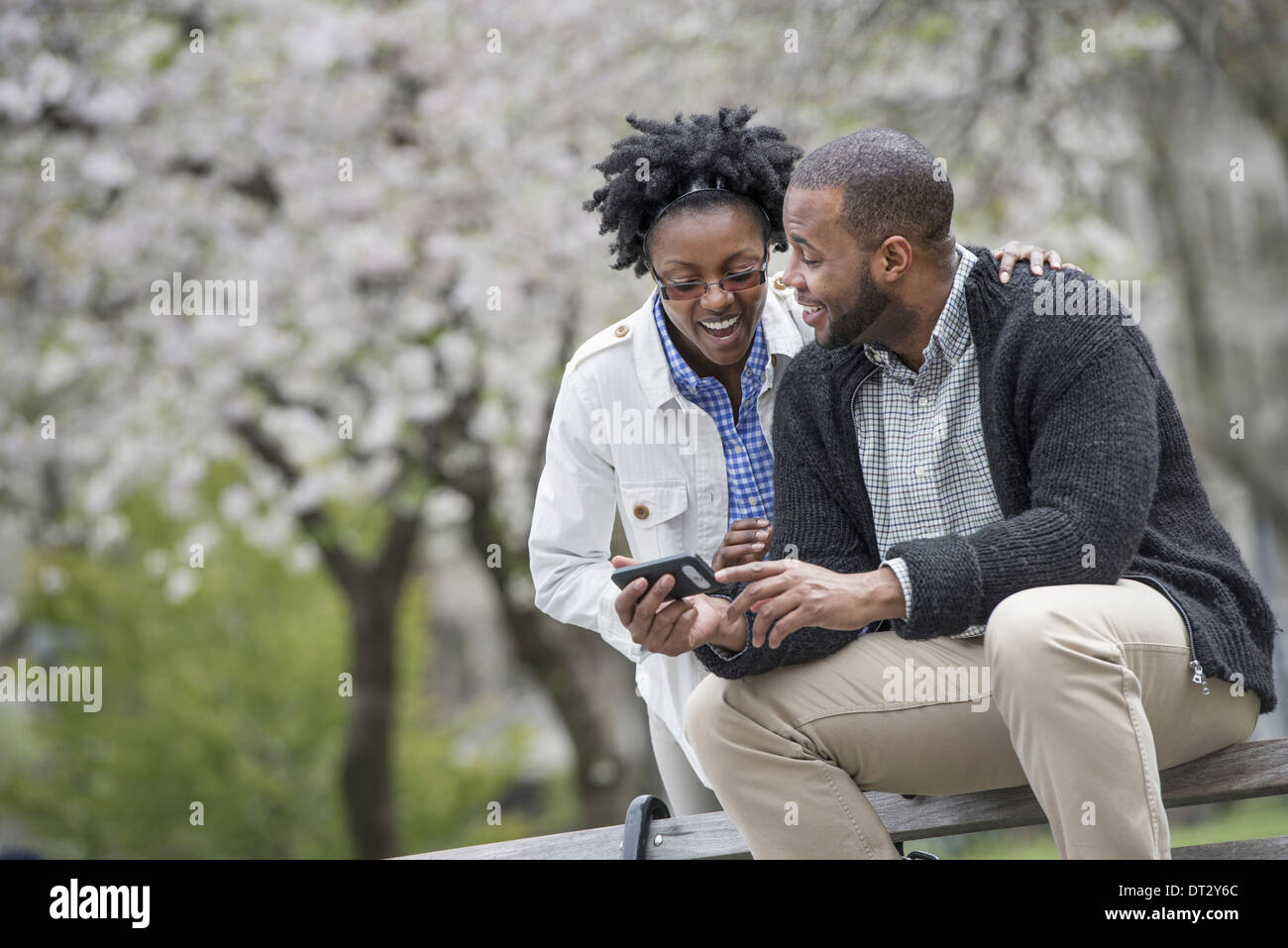 A couple sitting on a bench one holding a phone - Stock Image