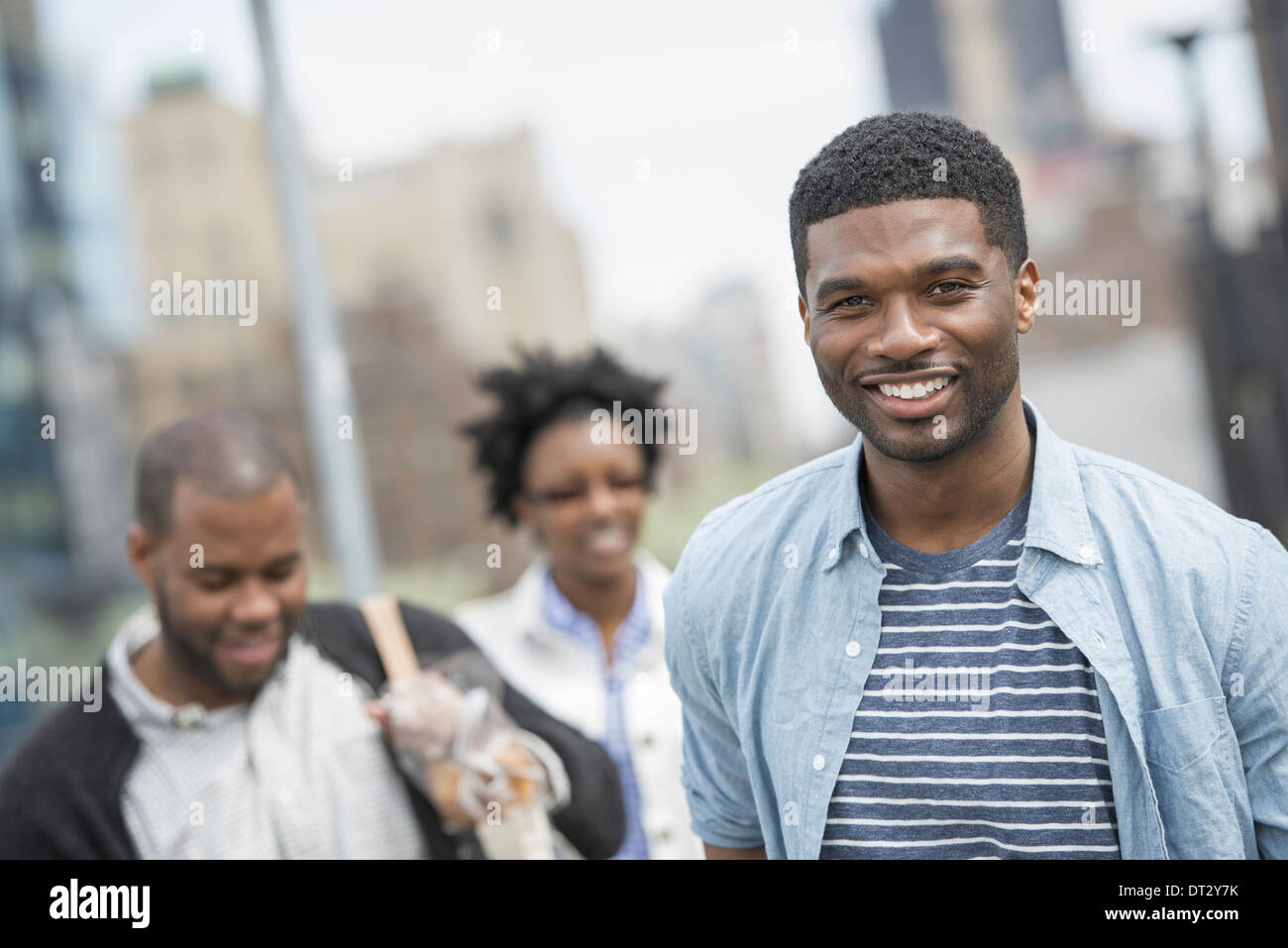 Three people a couple and a young man - Stock Image