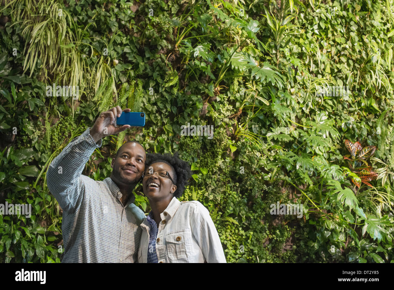 A couple standing in front of a wall covered with lush thick foliage - Stock Image