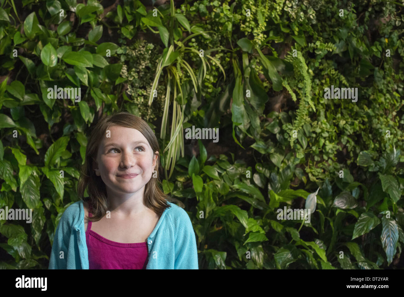 city in spring An urban lifestyle A young girl standing in front of a wall covered with ferns and climbing plants - Stock Image