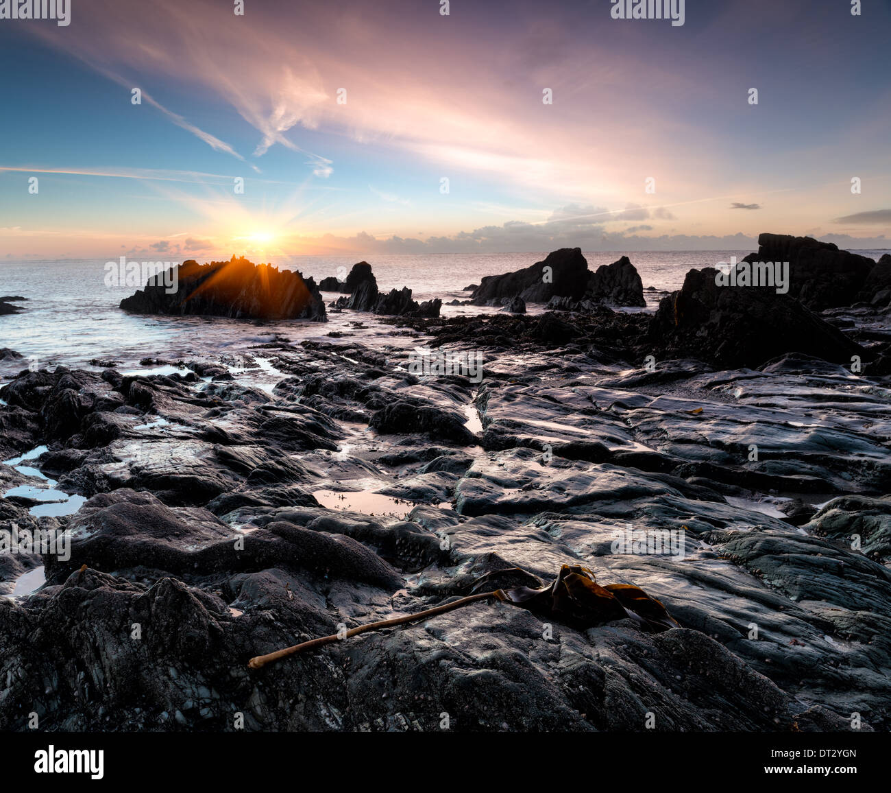 Ocean sunrise on a rocky beach at Looe in south Cornwall - Stock Image