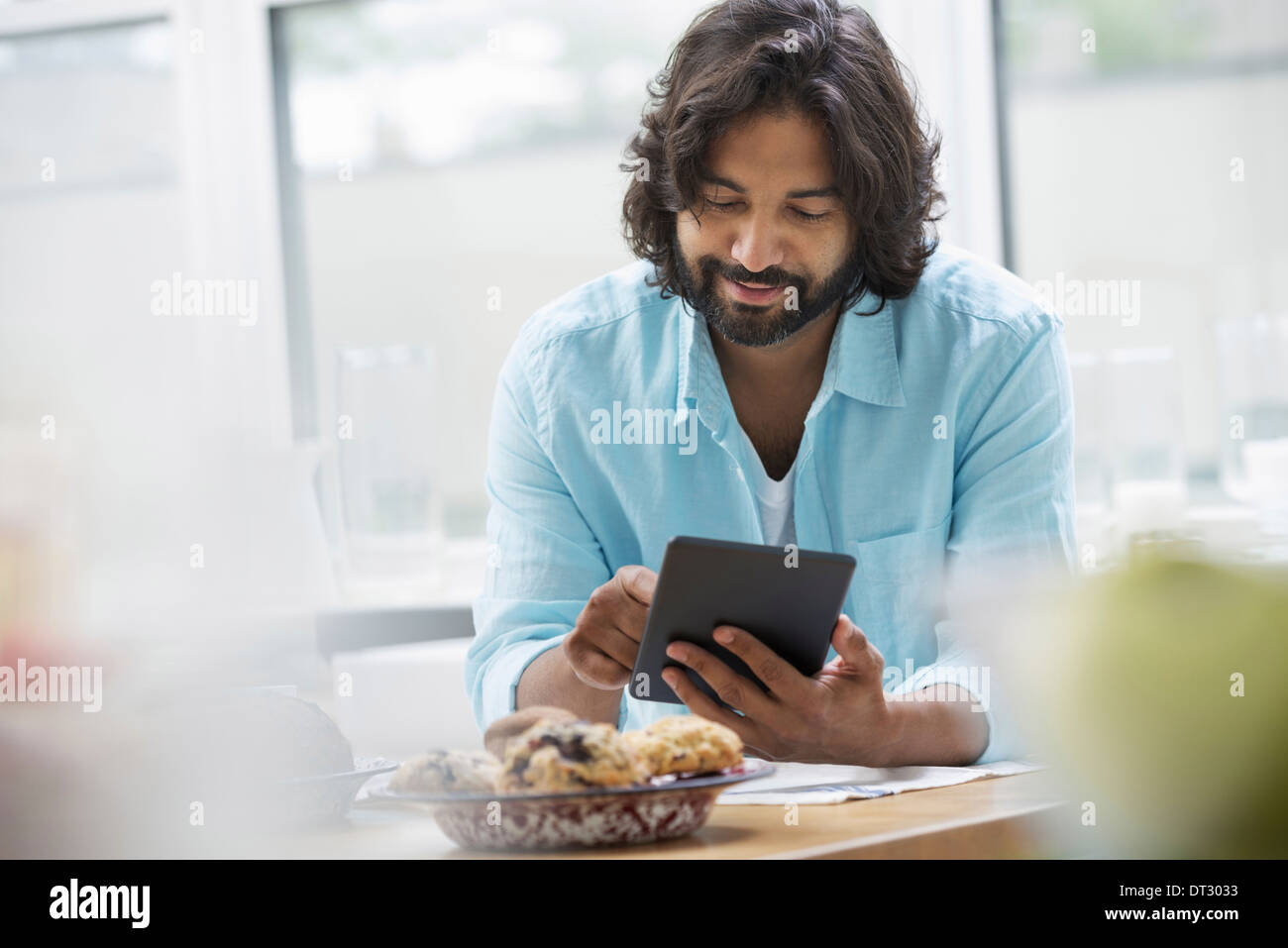 An office or apartment interior in New York City A bearded man in a turquoise shirt using a digital tablet - Stock Image