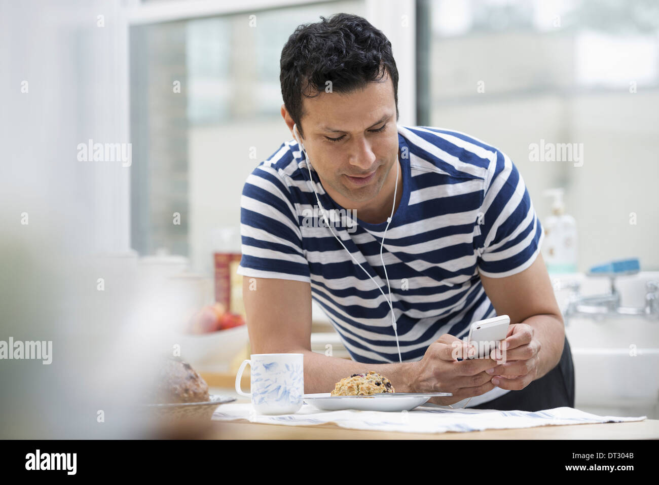 An office or apartment interior in New York City A man in a striped tee shirt leaning on the breakfast bar - Stock Image