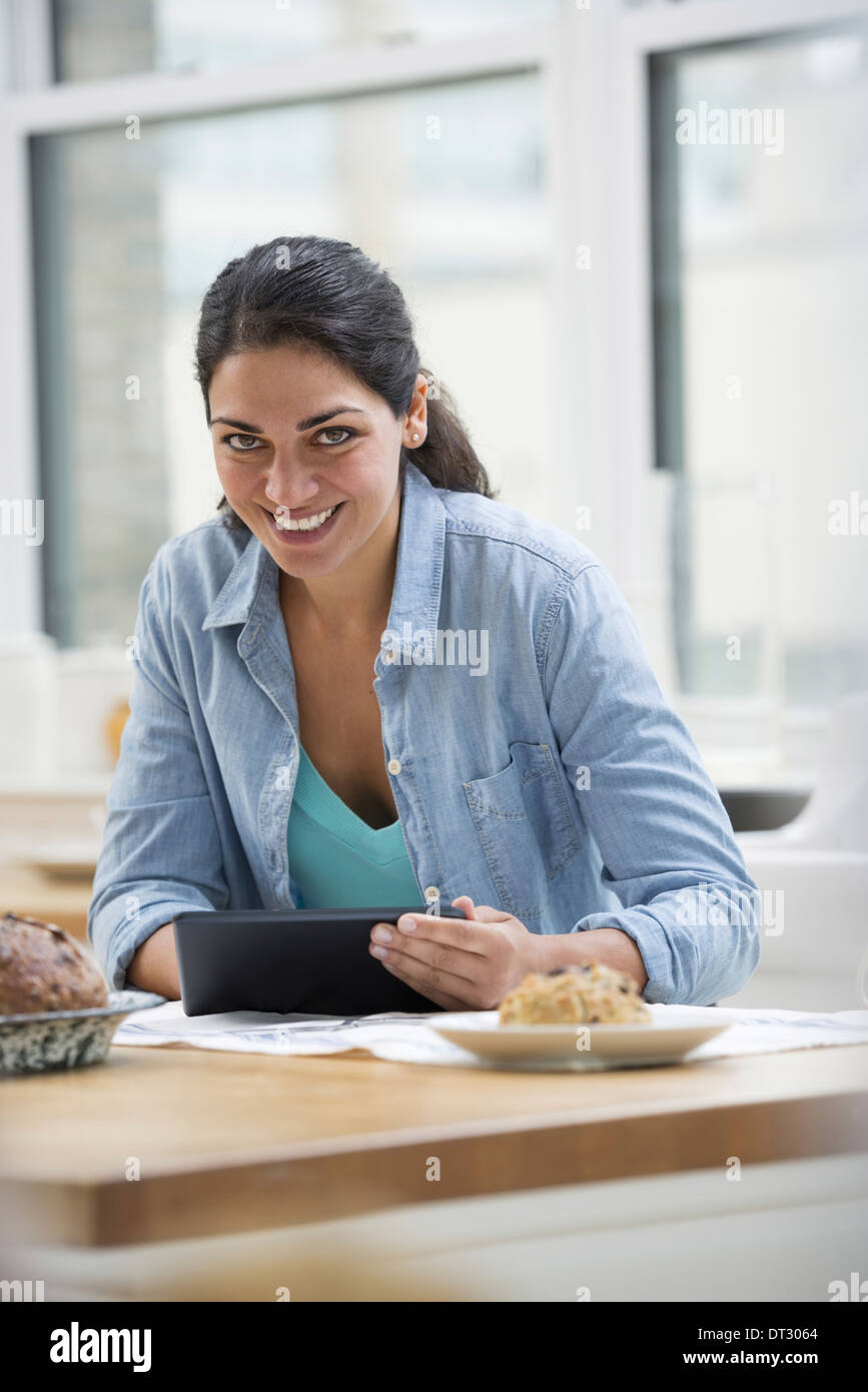 An office or apartment interior in New York City A young woman in a denim shirt using a digital tablet - Stock Image