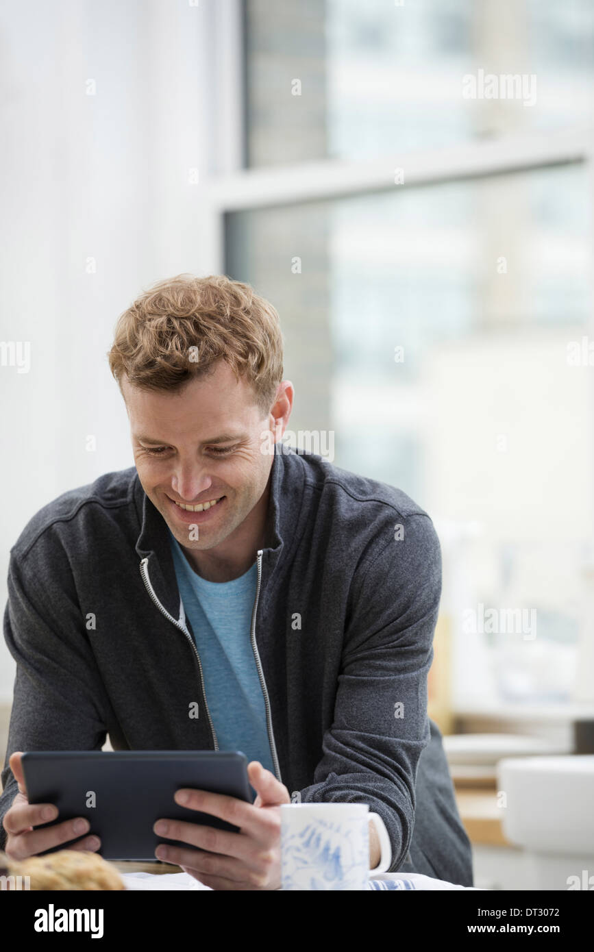 An office or apartment interior in New York City A man in a sweatshirt top using a digital pad Leaning on a breakfast bar - Stock Image