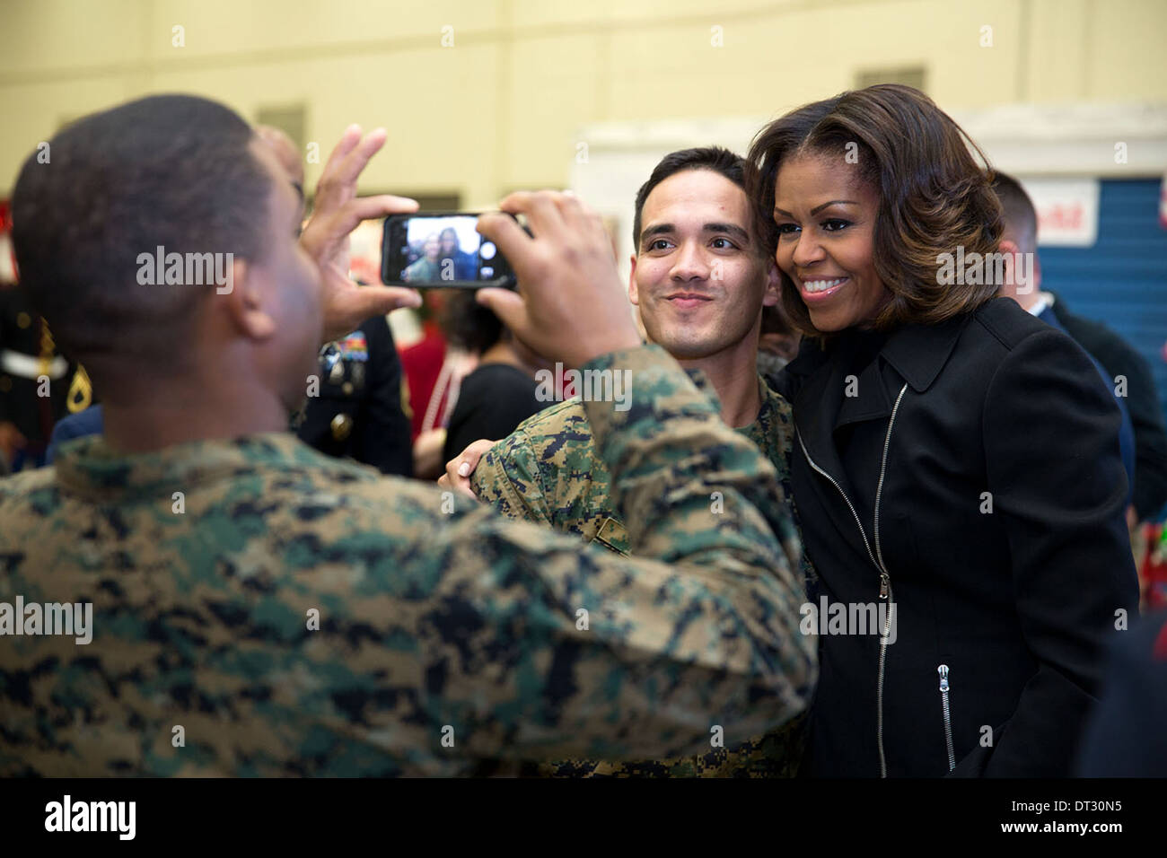 US First Lady Michelle Obama poses for a picture with service members after a Toys for Tots service project at the Joint Base Anacostia-Bolling Toys for Tots Distribution Center December 19, 2013 in Washington, DC. - Stock Image