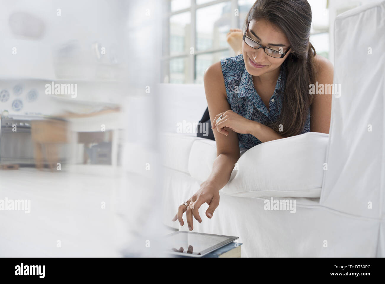 One person sitting comfortably in a quiet airy office environment Using a digital tablet - Stock Image