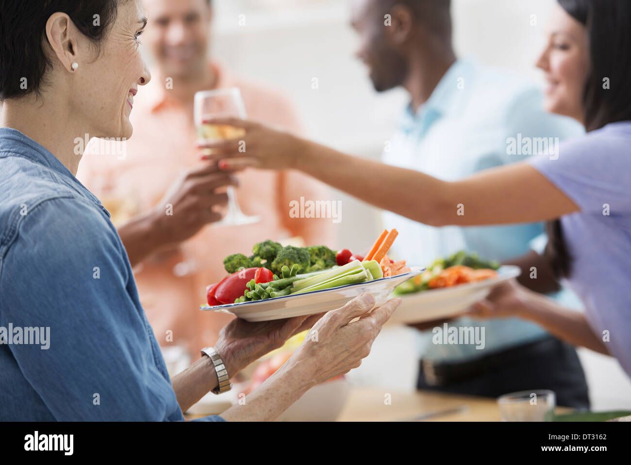 A working lunch a salad buffet A woman holding out a glass of wine and a plate of food - Stock Image