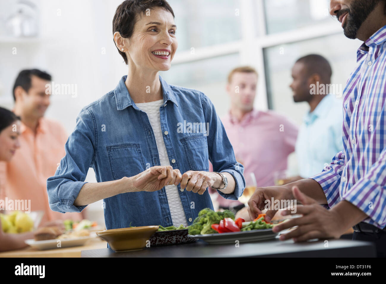 An open plan office A working lunch a salad buffet of mixed ages and ethnicities meeting together Stock Photo