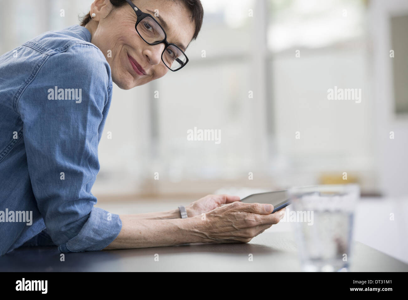 Professionals in the office A light and airy place of work A mature woman in a blue denim shirt holding a digital tablet - Stock Image
