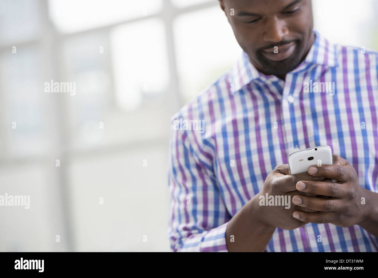 Professionals in the office A light and airy place of work A man in a checked shirt using a smart phone - Stock Image