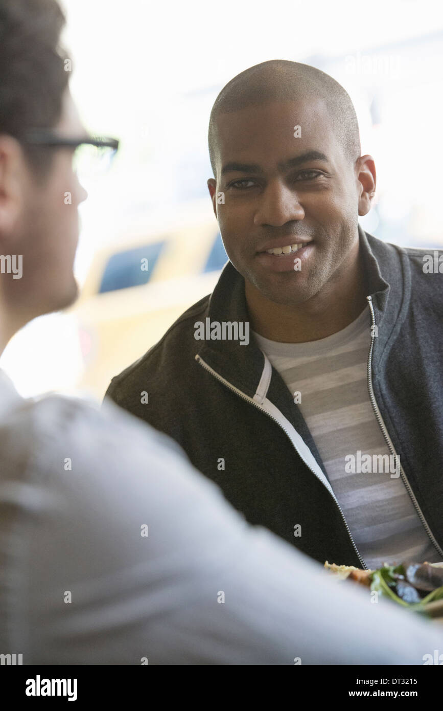 Two men seated at a cafe talking to each other - Stock Image