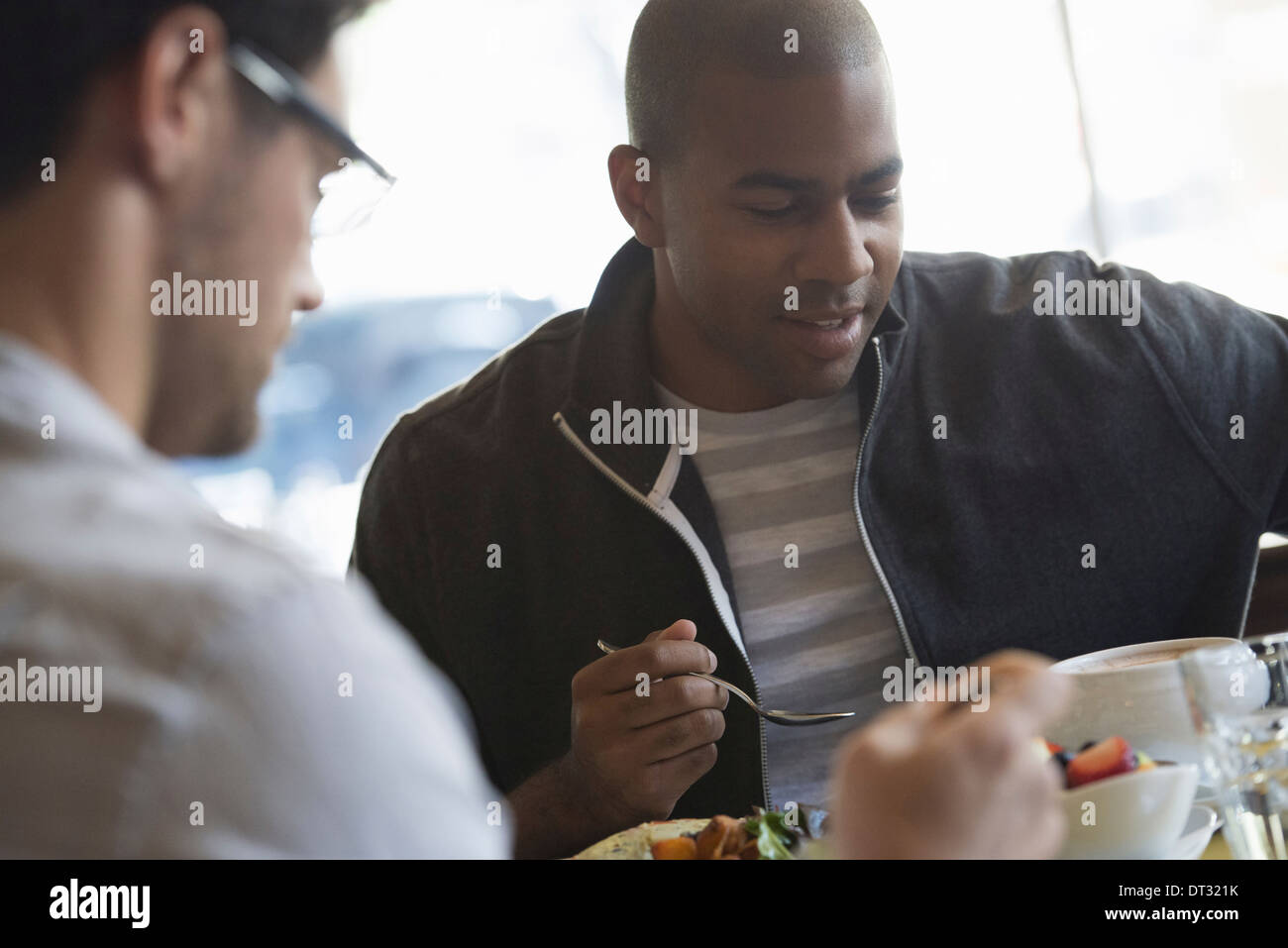 Two men seated at a cafe table having a meal - Stock Image