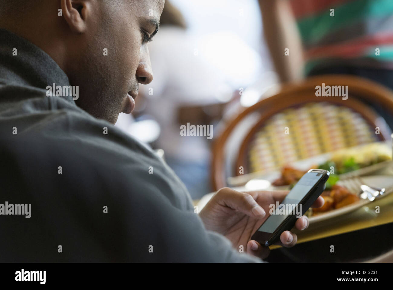 A man seated in a cafe checking his smart phone - Stock Image