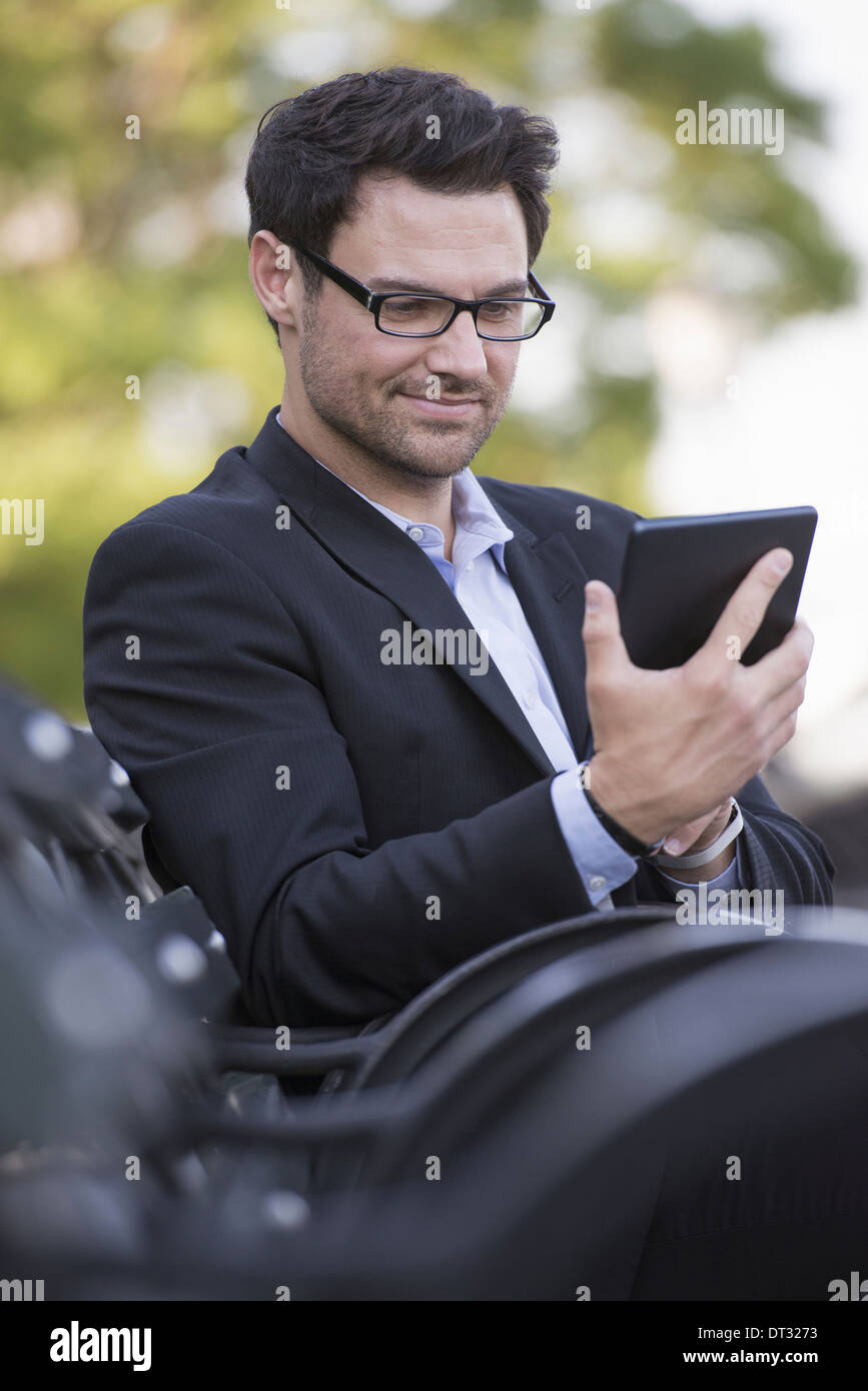 A man seated on a bench Using a digital tablet - Stock Image
