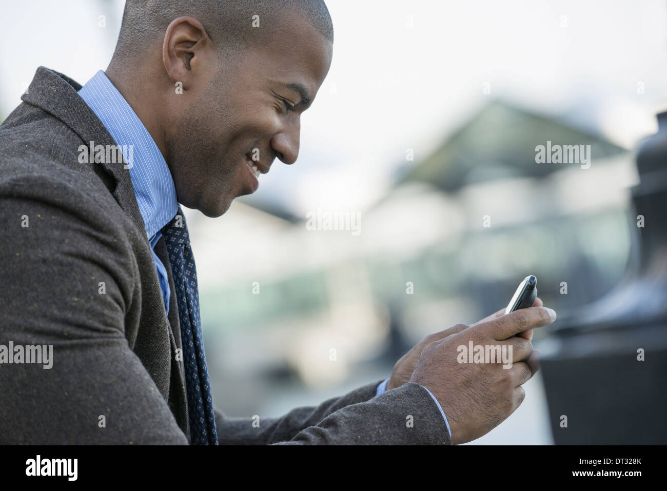 A man seated on a bench checking his smart phone - Stock Image