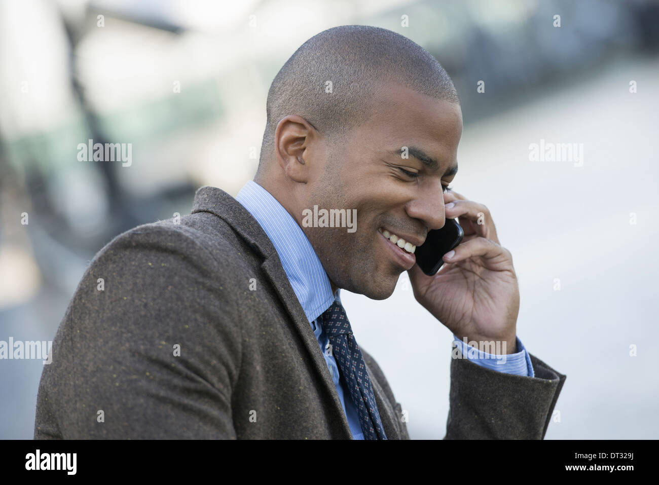 A man seated on a bench making a call on his smart phone - Stock Image