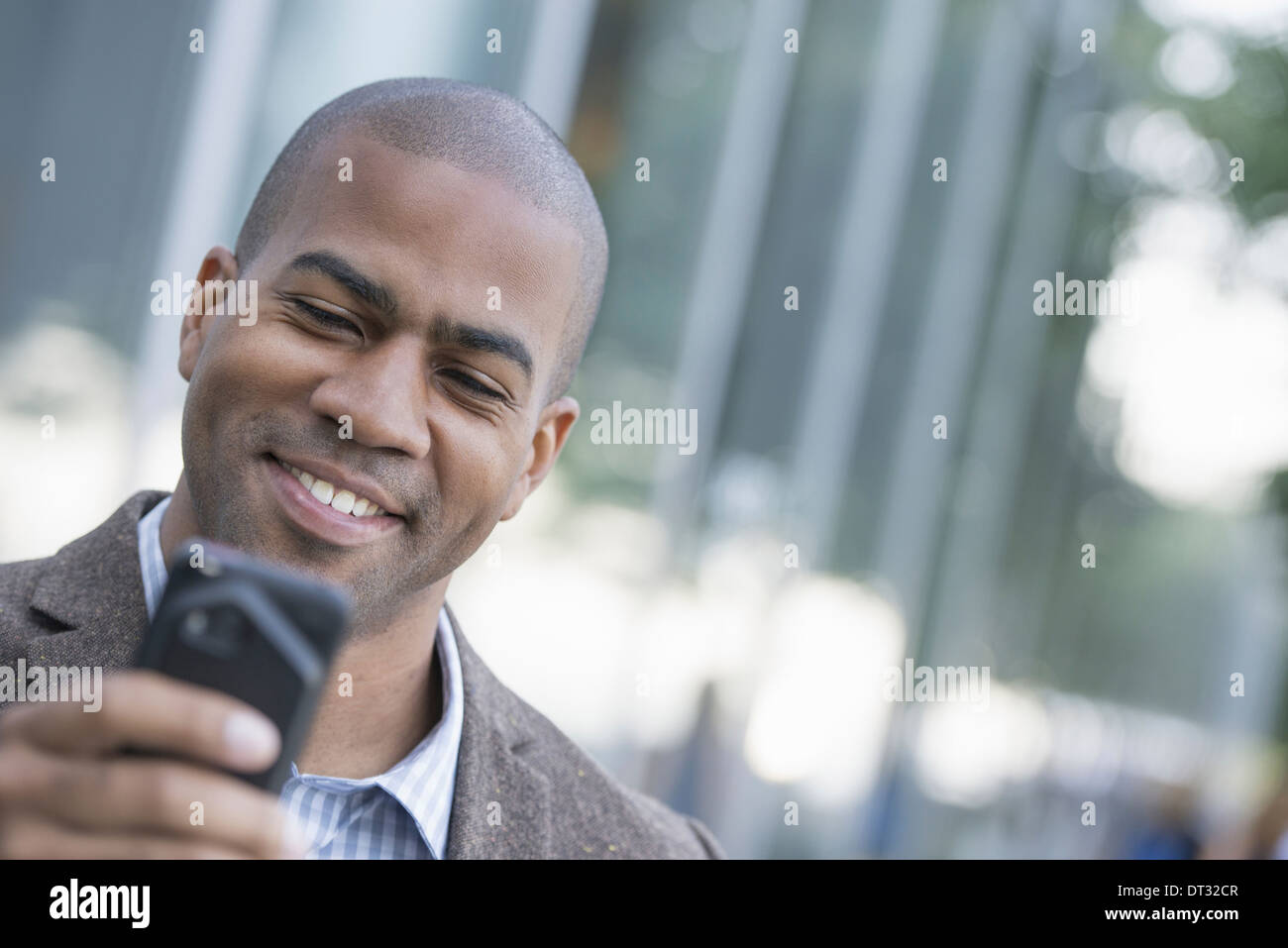 A man looking down at his smart phone - Stock Image