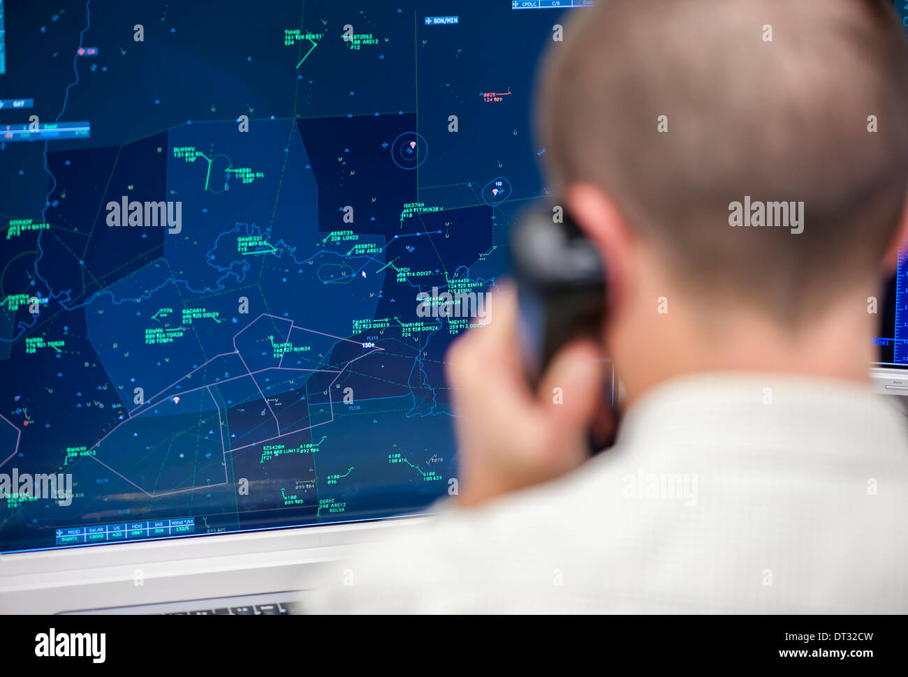 An air traffic controller in the air traffic control centre of 'Skyguide' is navigating aircrafts through Switzerland's airspace - Stock Image