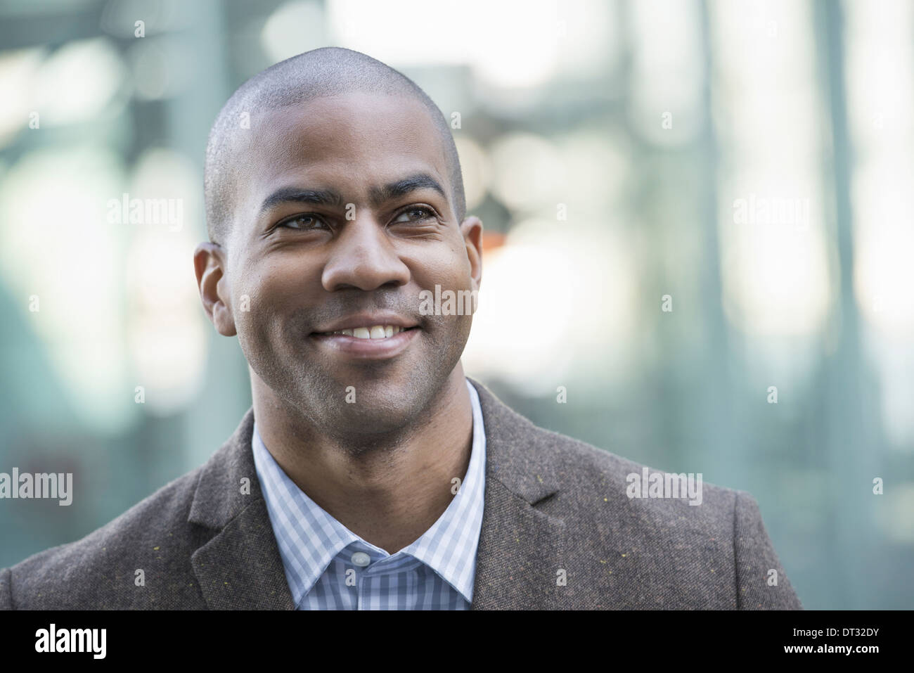 A man in jacket and tie smiling and looking into the distance - Stock Image