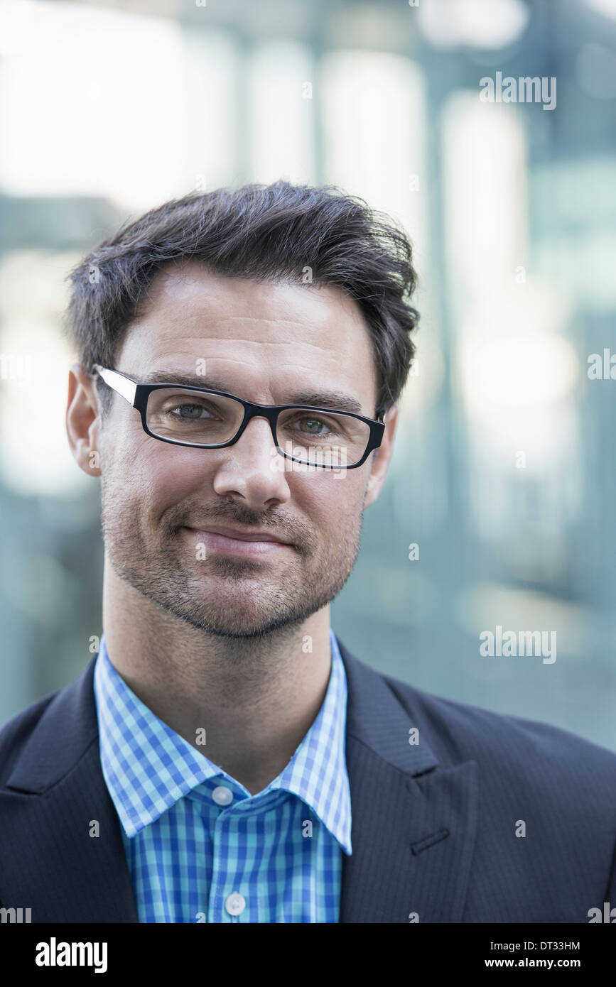 A man in a blue shirt and dark jacket smiling - Stock Image
